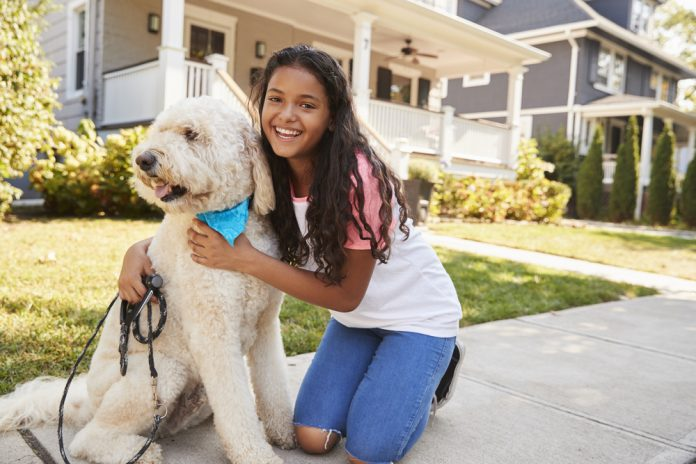 First-Time Home Buyer's Daughter? Girl kneeling and hugging a white dog on the side walk.