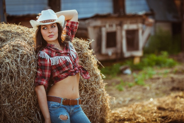 USDA Loans: Home Requirements Image of young woman next to a bale